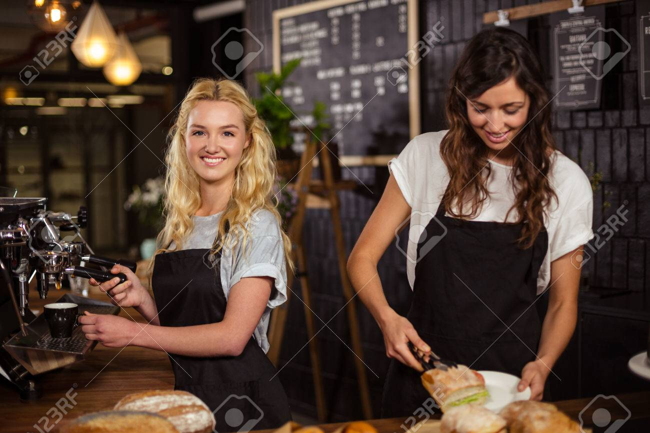 Pretty waitresses behind the counter working at the coffee shop Standard-Bild - 52878265