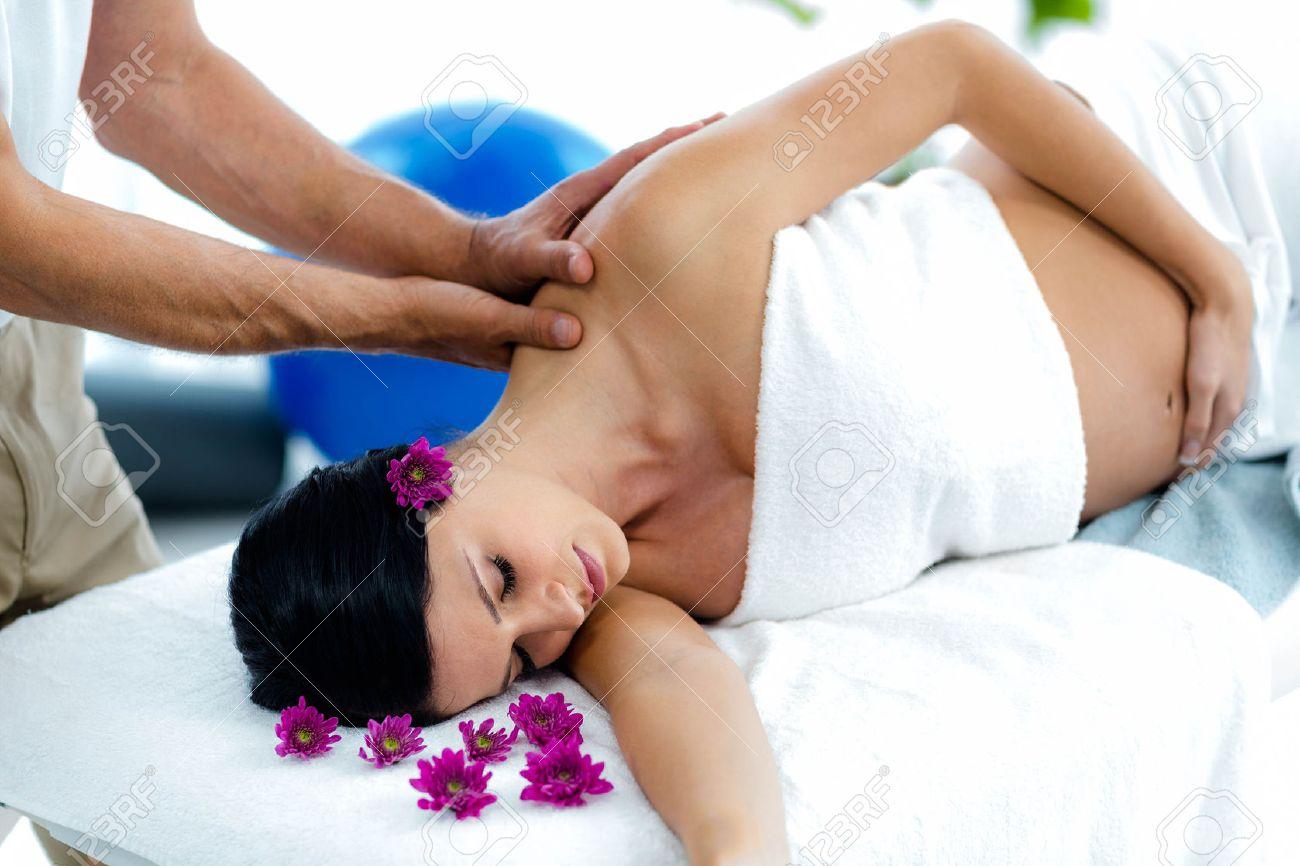 Pregnant woman receiving a back massage from masseur at health spa Standard-Bild - 53225474