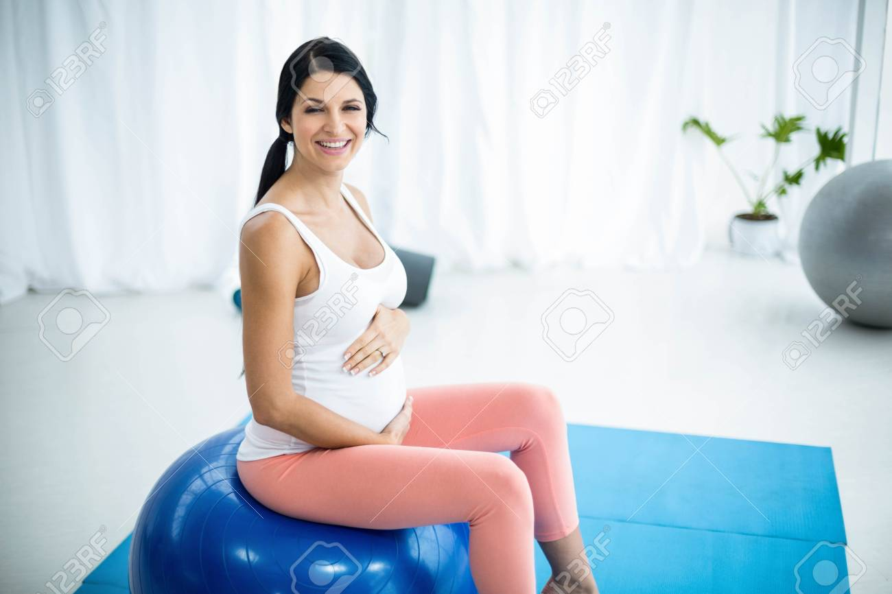 Foto de archivo - Retrato de mujer embarazada haciendo ejercicio mientras  está sentado en la pelota de ejercicios en casa cbc4842e5696