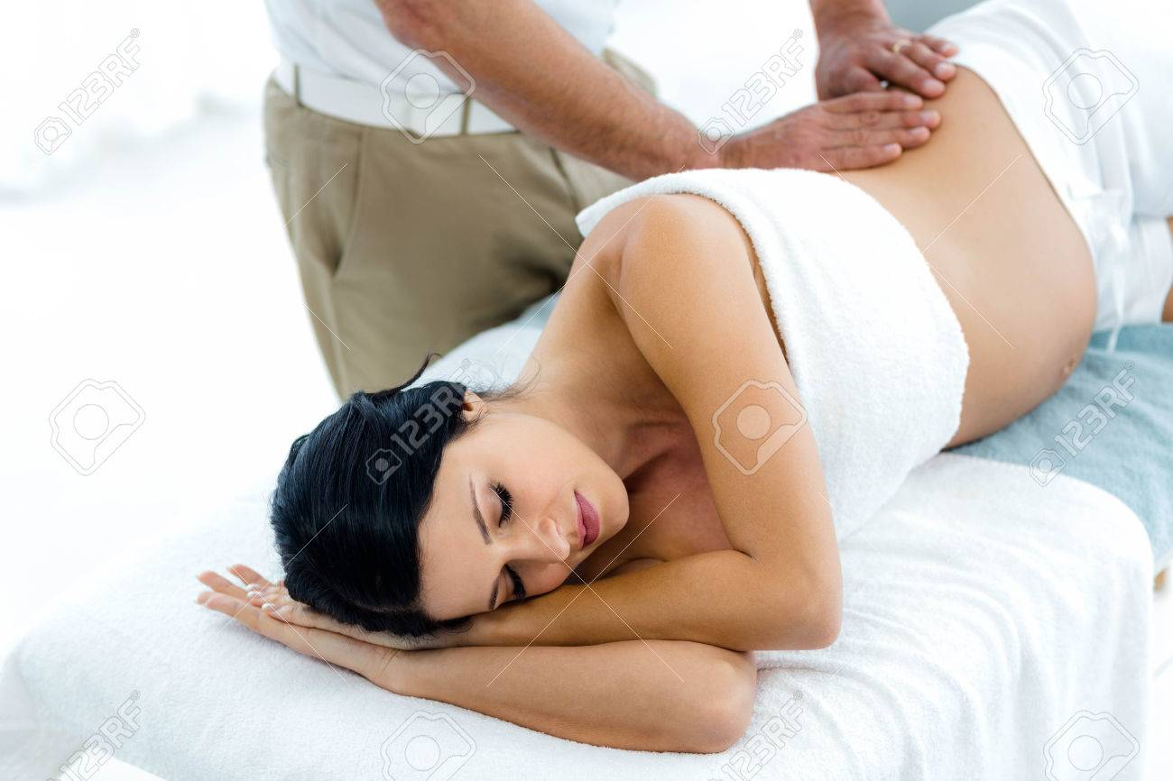 Pregnant woman receiving a back massage from masseur at home Stock Photo - 53318159