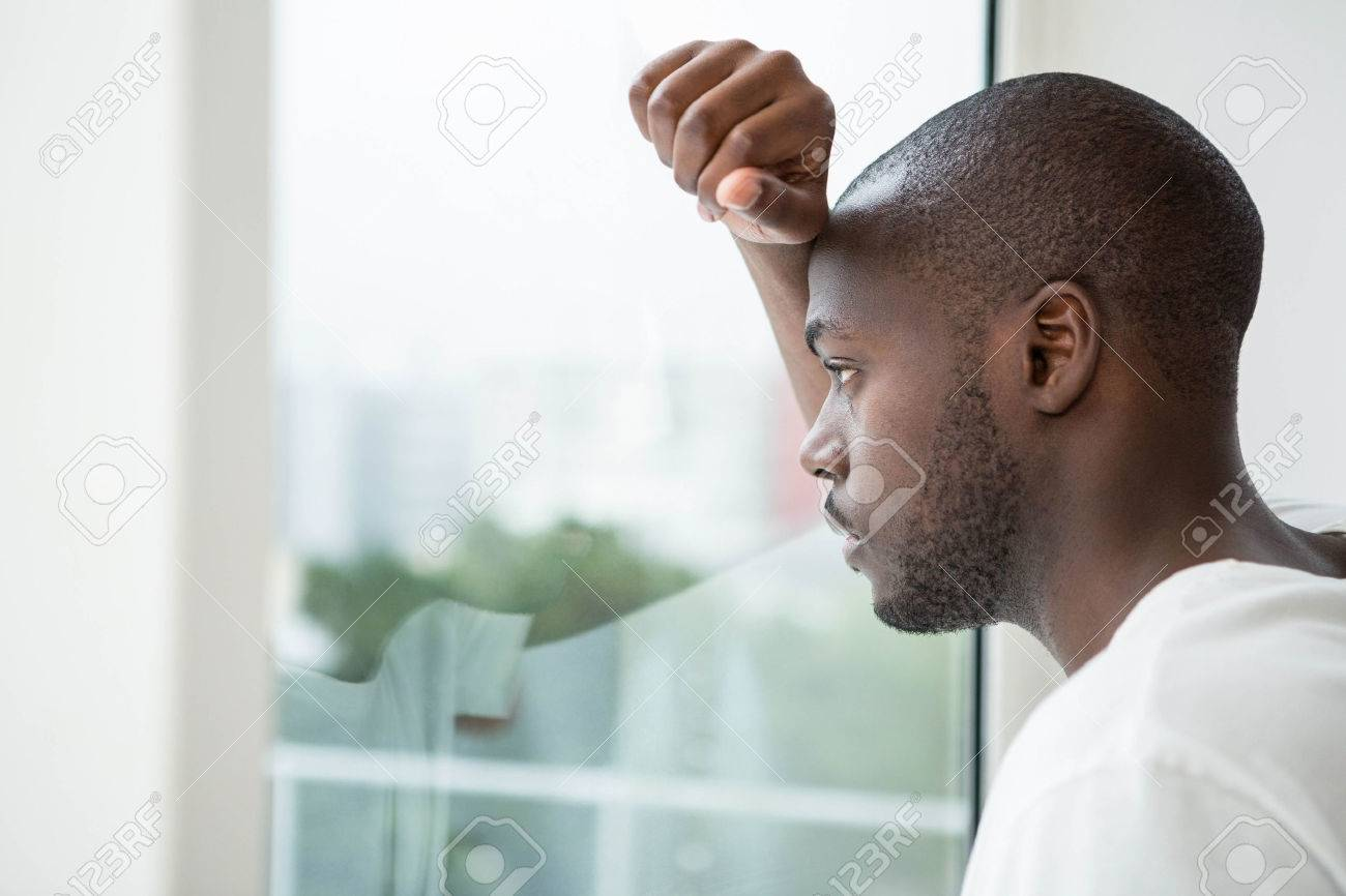 Thoughtful man looking out the window in bedroom at home Stock Photo - 53276170