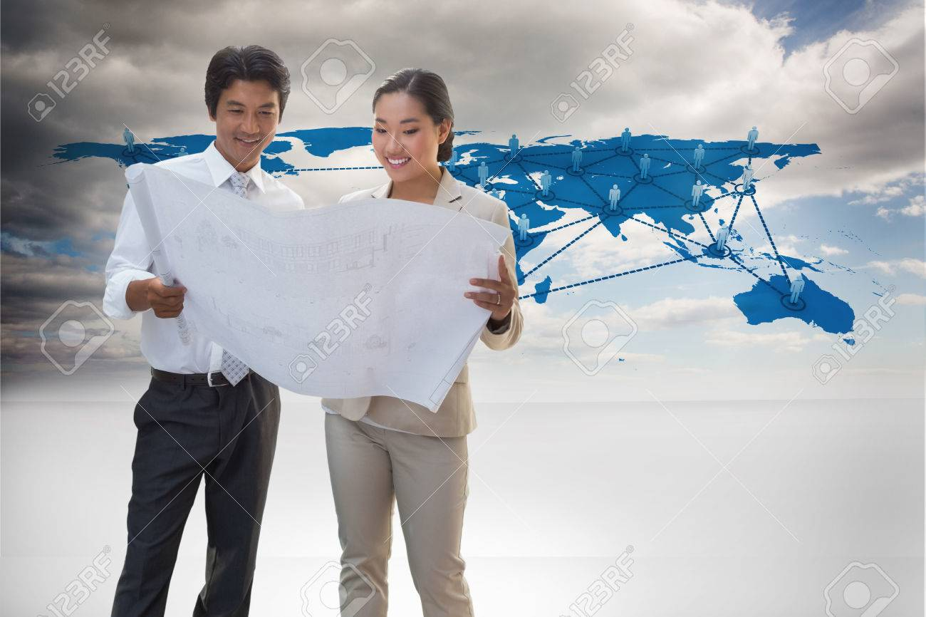 Estate agent looking at blueprint with potential buyer against estate agent looking at blueprint with potential buyer against view of a global map stock photo malvernweather Images