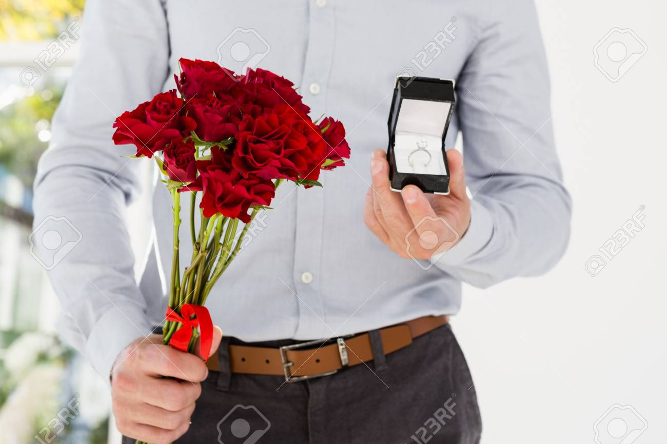 Happy Young Man Holding Engagement Ring And Flower Bouquet Stock ...
