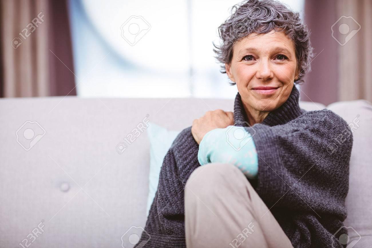 Portrait de femme souriante d'âge mûr assis sur le canapé à la maison Banque d'images - 53993655