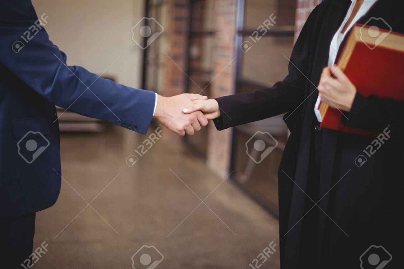 Midsection of female lawyer handshaking with client while standing in office Standard-Bild - 54310483