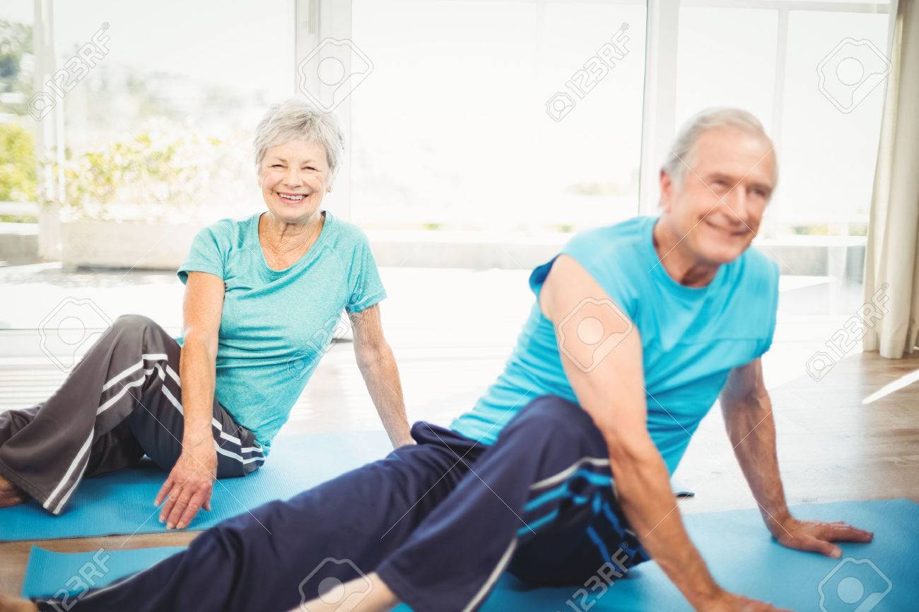 Happy senior couple doing yoga on exercise mat at home Standard-Bild - 53958683