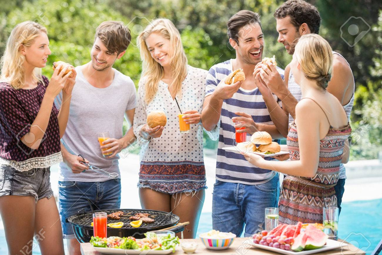 Group of friends having hamburgers and juice at outdoors barbecue party Standard-Bild - 54328100