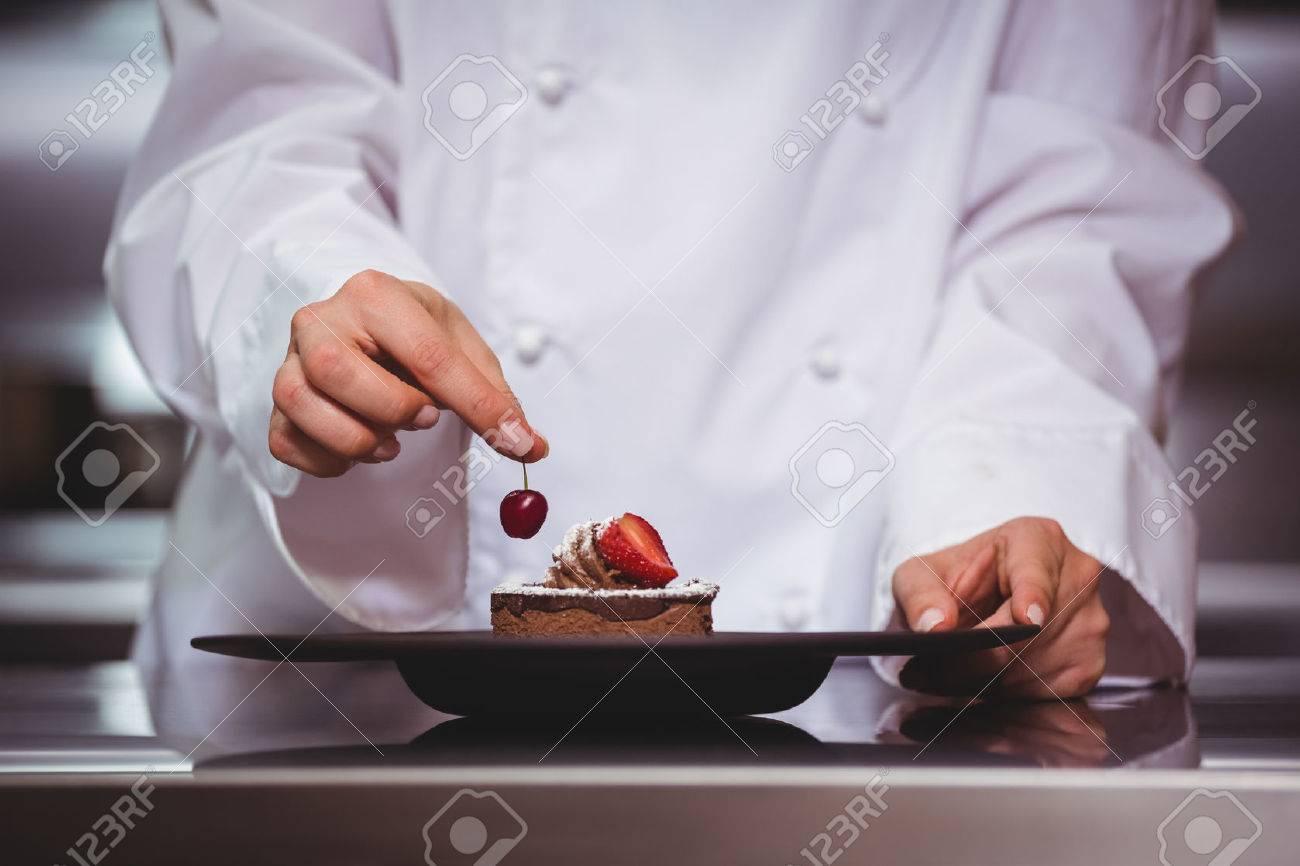 Chef de mettre une cerise sur un dessert dans une cuisine commerciale Banque d'images - 54335718