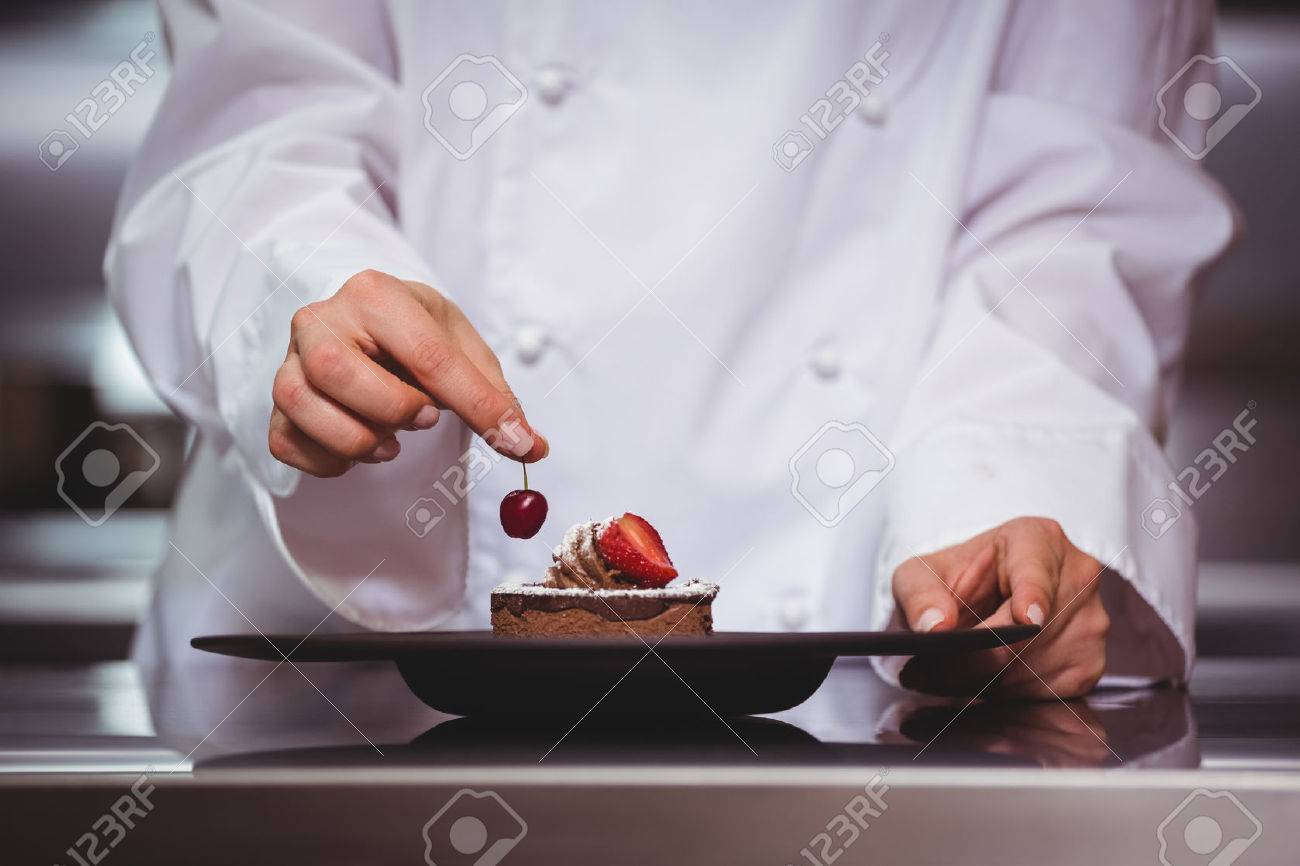 Chef putting a cherry on a dessert in a commercial kitchen Standard-Bild - 54335718