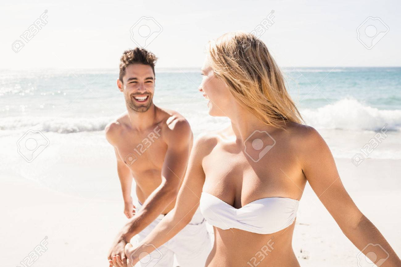 Young couple holding hands on the beach Standard-Bild - 54338159