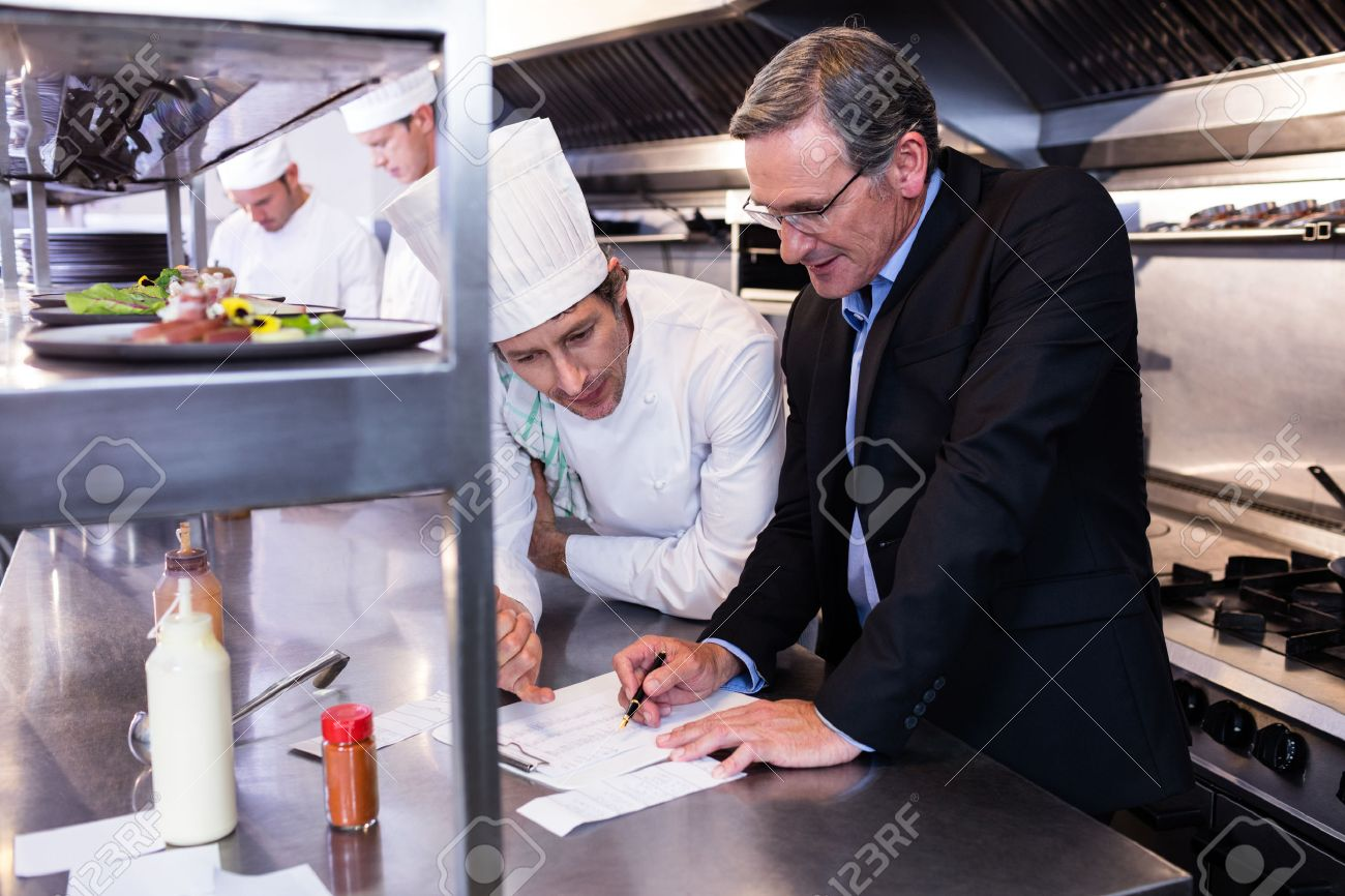 Male restaurant manager writing on clipboard while interacting to head chef in commercial kitchen Standard-Bild - 54391232