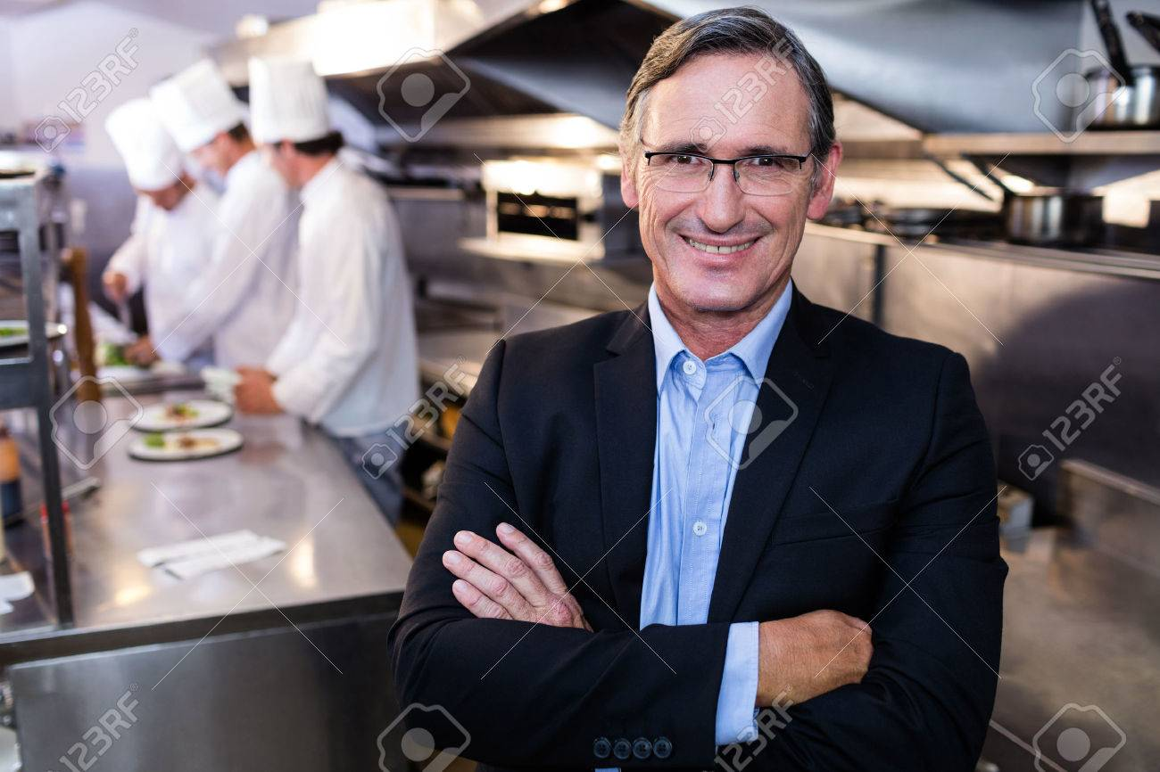 Male restaurant manager standing with arms crossed in commercial kitchen Standard-Bild - 54391241