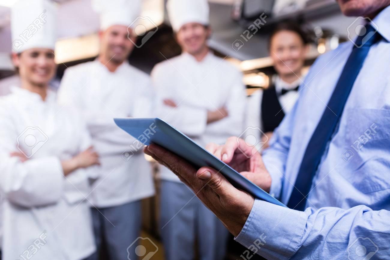 Mid section of restaurant manager using digital tablet in commercial kitchen Standard-Bild - 54391199