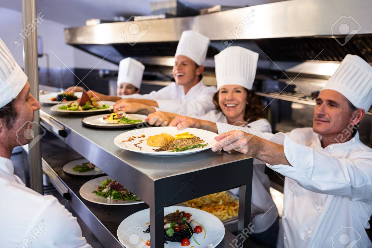 Chefs handing dinner plates through order station in the commercial kitchen Stock Photo - 54391425  sc 1 st  123RF.com & Chefs Handing Dinner Plates Through Order Station In The Commercial ...