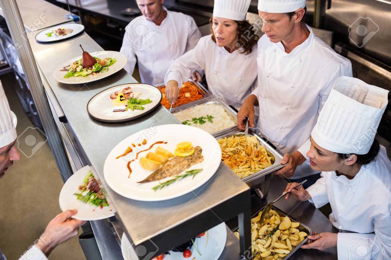 Chefs handing dinner plates through order station in the commercial kitchen Stock Photo - 54391443  sc 1 st  123RF.com & Chefs Handing Dinner Plates Through Order Station In The Commercial ...