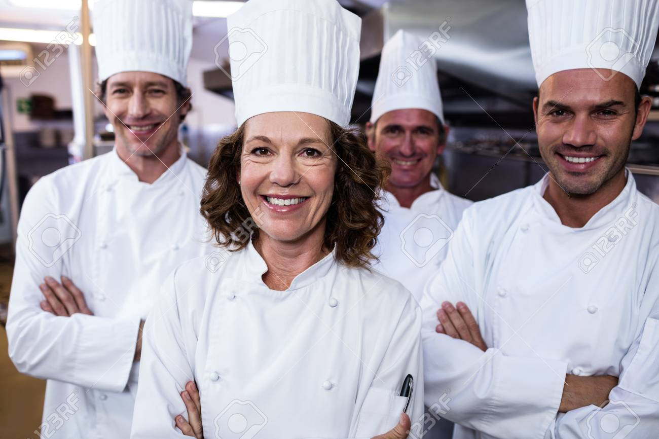 Group Of Happy Chefs Smiling At The Camera In A Kitchen Wearing