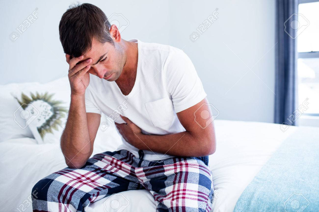 Young man sitting with stomach pain on bed in bedroom Banque d'images - 54392875