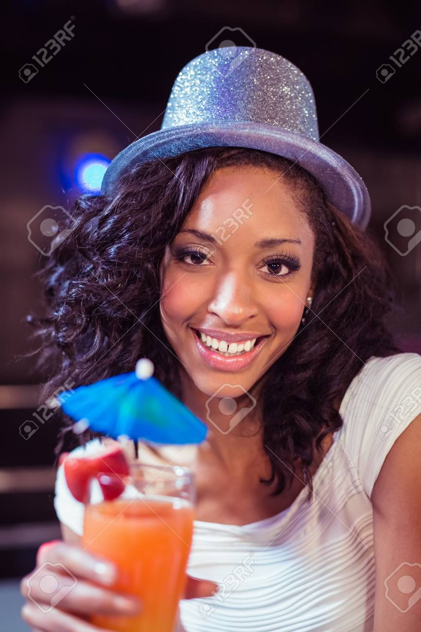 Pretty girl with cocktail and glitter hat in a club Stock Photo - 54392488