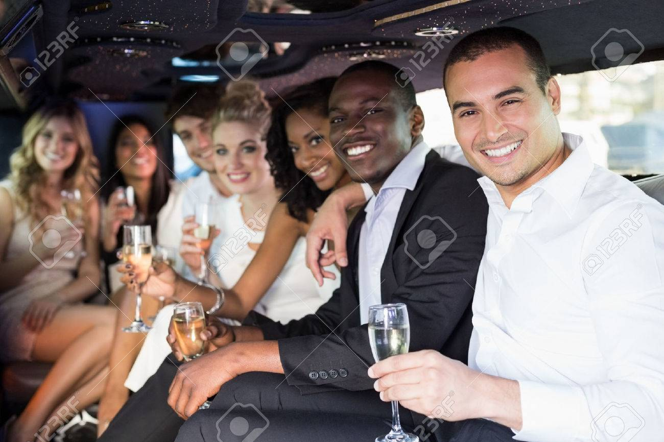 Well dressed people drinking champagne in a limousine on a night out Banque d'images - 54644538