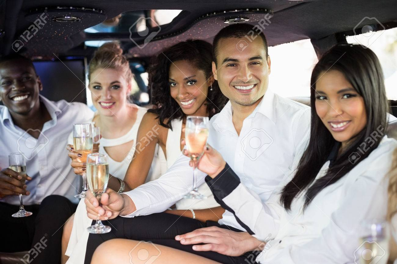 Well dressed people drinking champagne in a limousine on a night out Stock Photo - 54391544