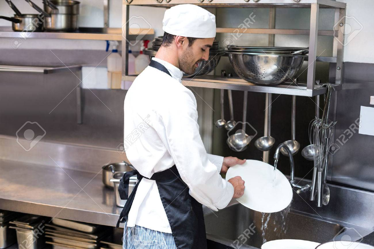 Handsome employee doing dishes in commercial kitchen Standard-Bild - 54556153