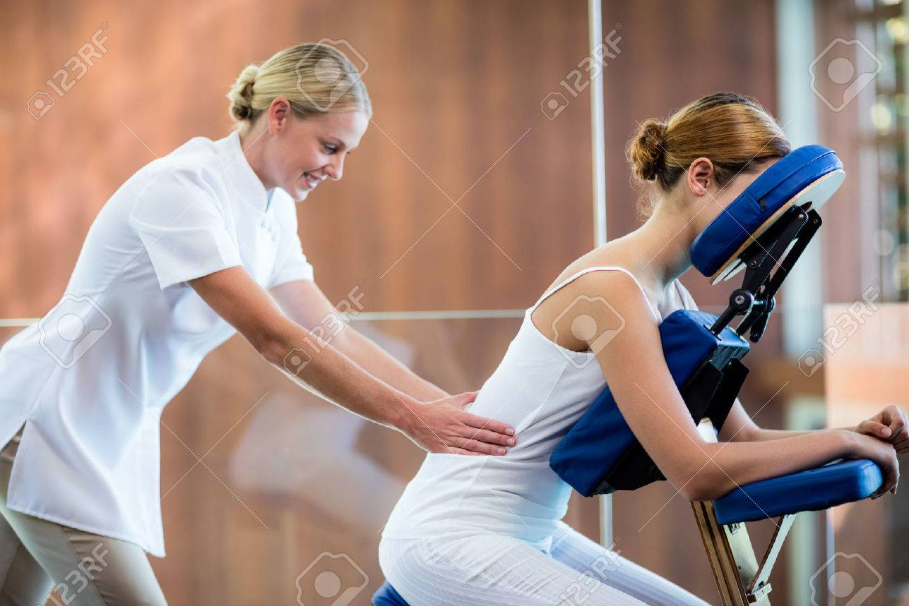 Woman receiving massage in massage chair at spa Banque d'images - 54556619