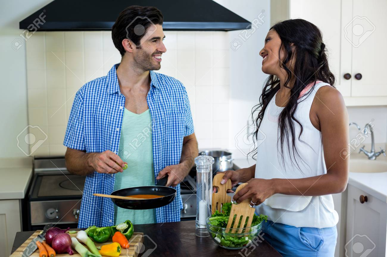 Young Couple Cooking Food Together In Kitchen At Home Stock Photo ...