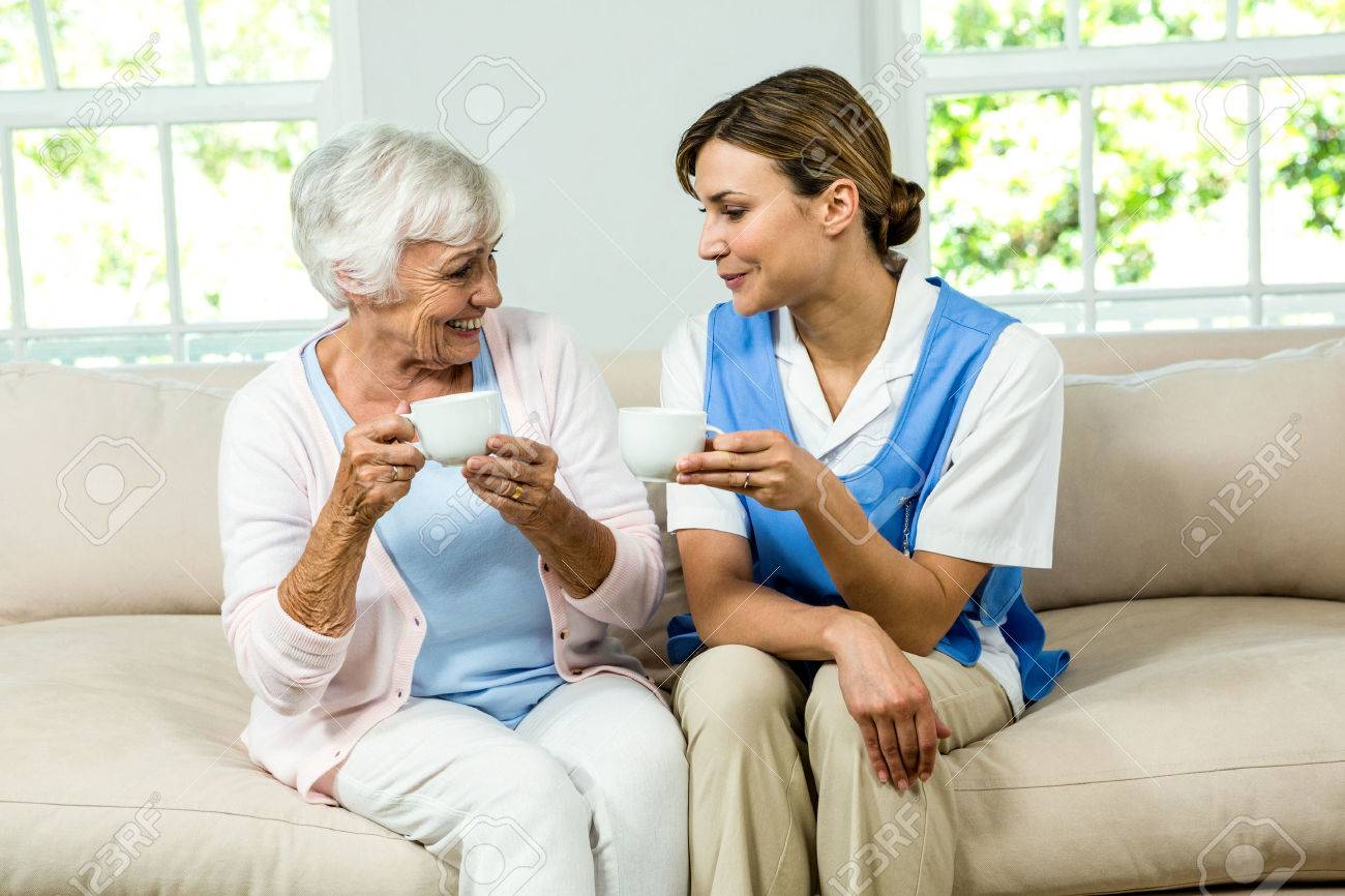 Smiling nurse and senior woman holding coffee cups on sofa at home Stock Photo - 54969351