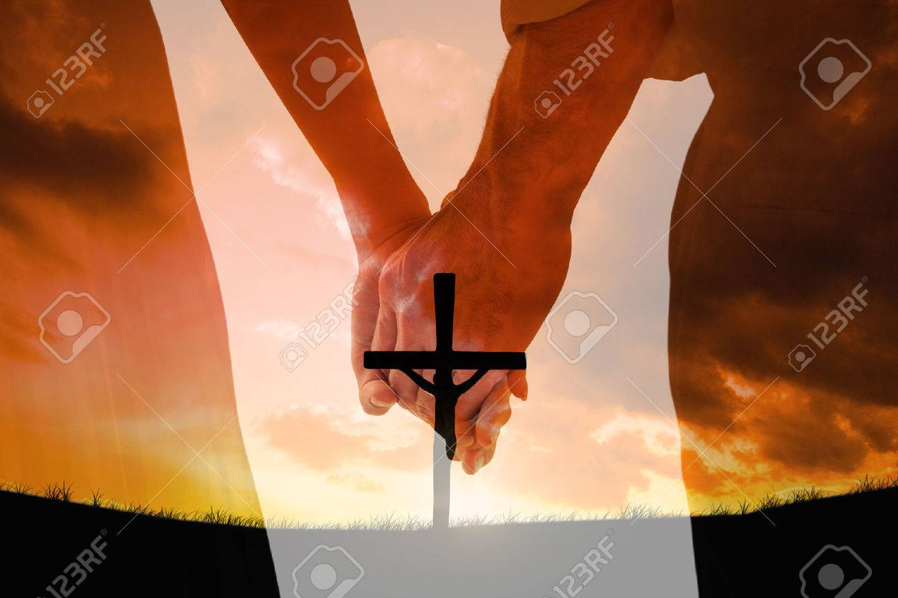 Mariée et le marié tenant la main fermer contre croix en forme de symbole de la religion sur le coucher du soleil ciel Banque d'images - 55068913