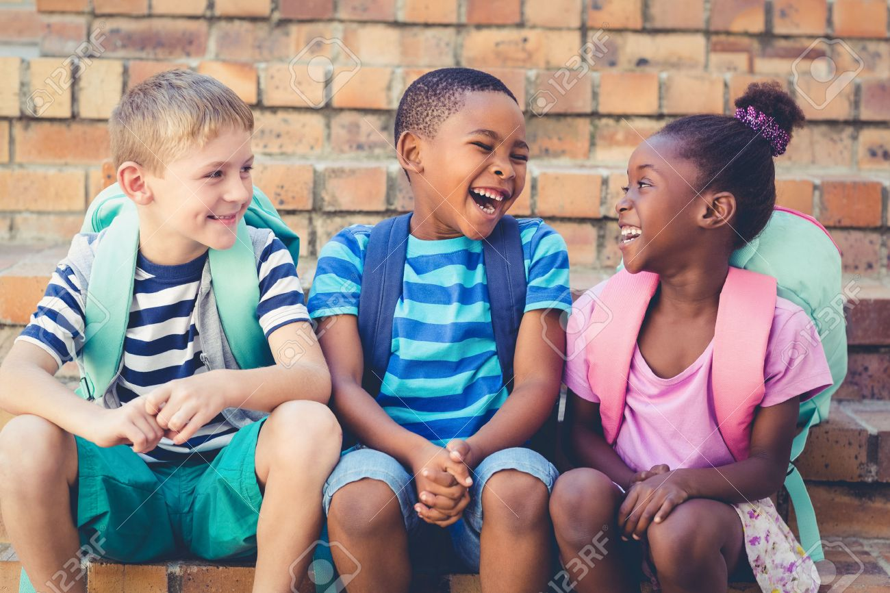Happy écoliers assis ensemble sur un escalier à l'école Banque d'images - 58210962