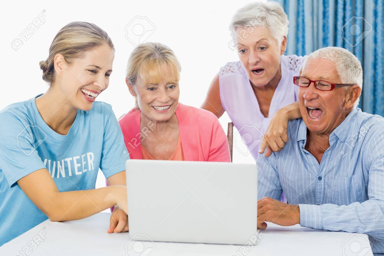 stock photo volunteer and seniors using a laptop in a retirement home