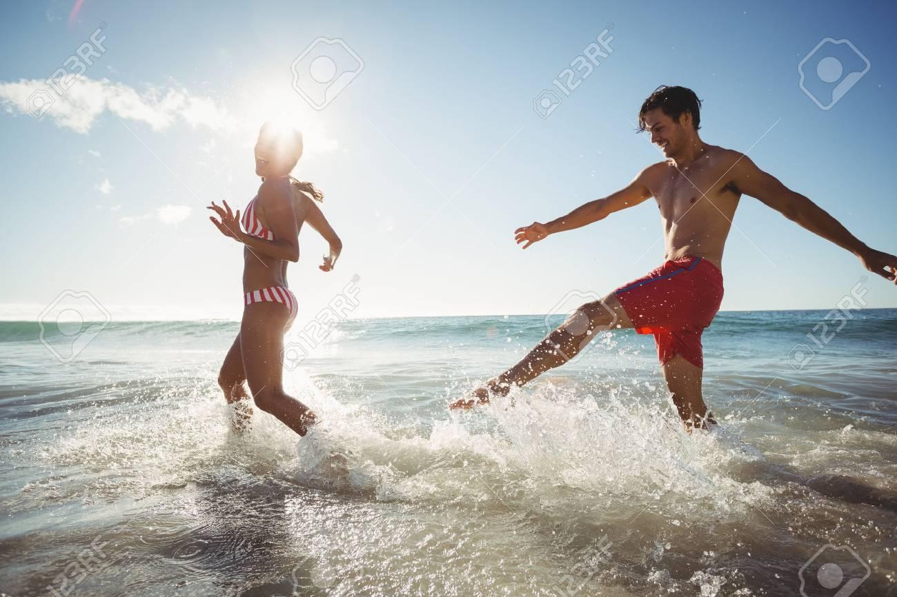 Feliz Pareja De Jovenes Jugando En El Agua En La Playa Fotos