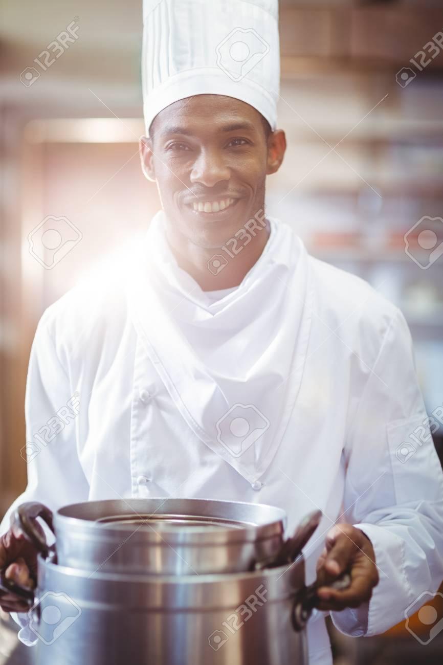 Porträt Der Lächelnden Koch In Der Küche Kochtopf Halten Lizenzfreie ...