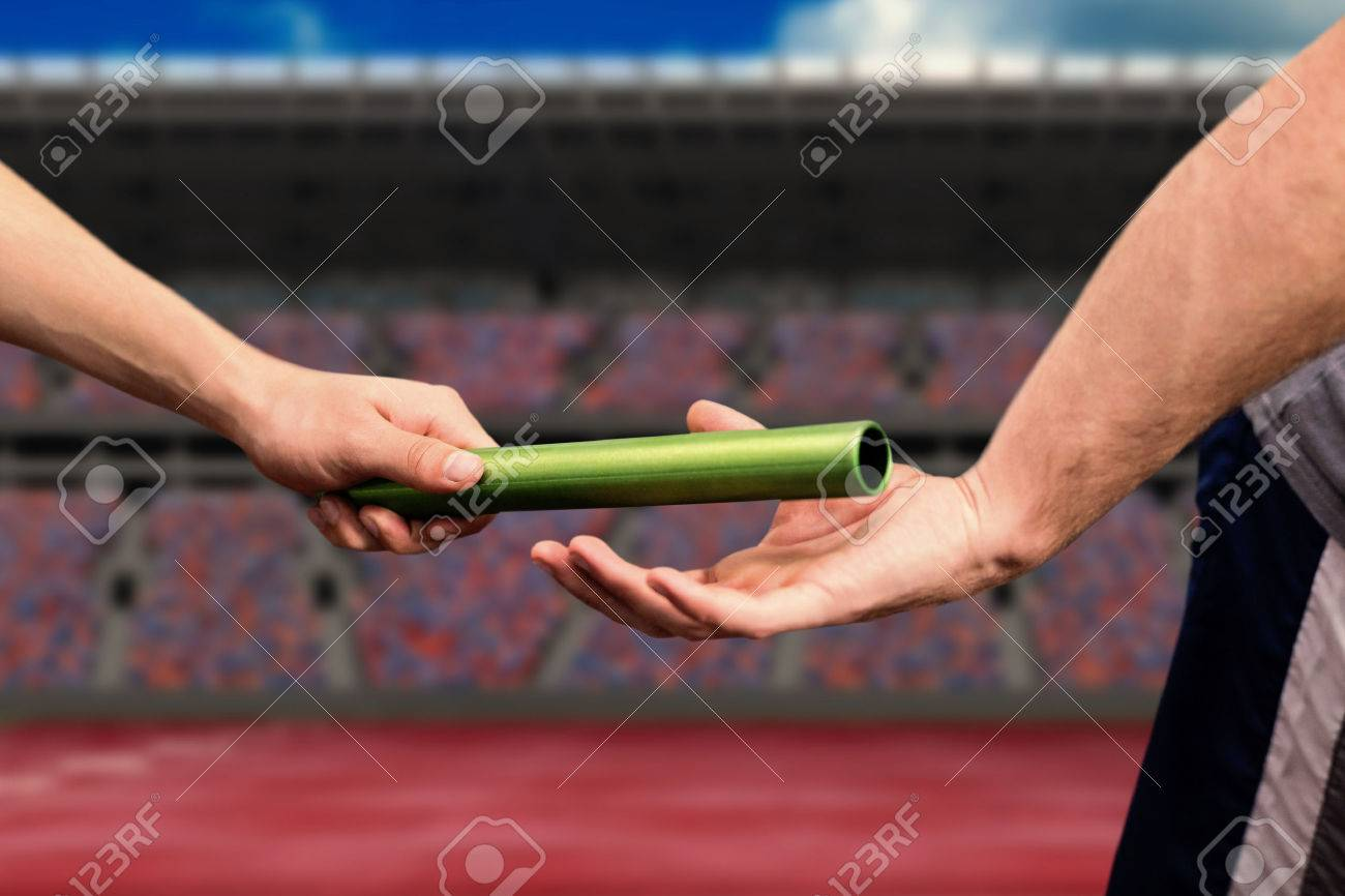 Man passing the baton to partner on track against athletic field on a stadium Stock Photo - 58882355