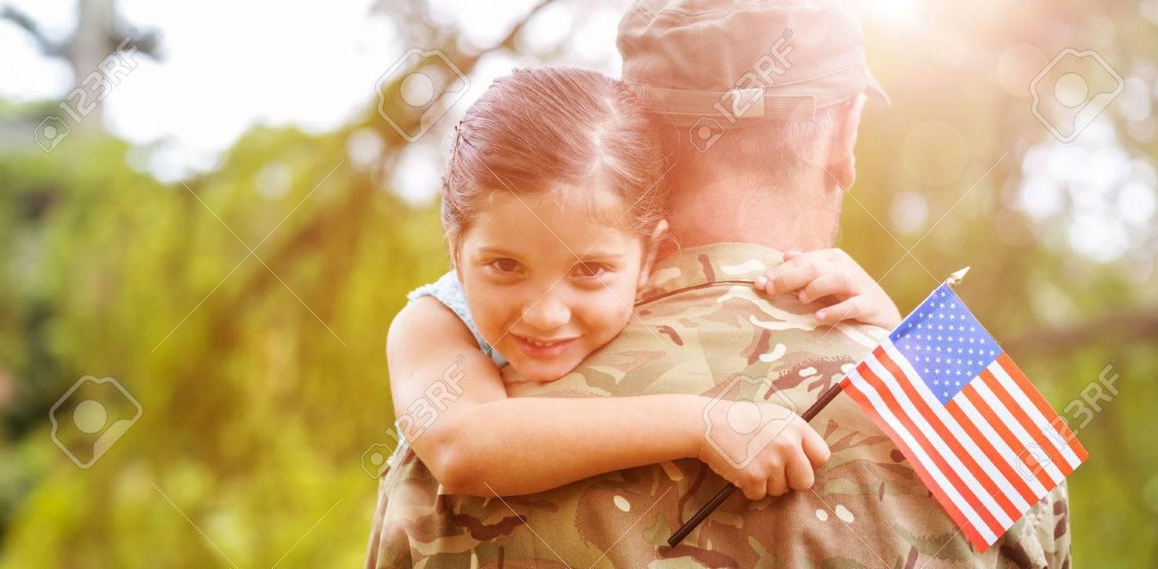 Portrait de jeune fille souriante tenant le drapeau américain tout en étreignant père officier de l'armée dans le parc Banque d'images - 58741812