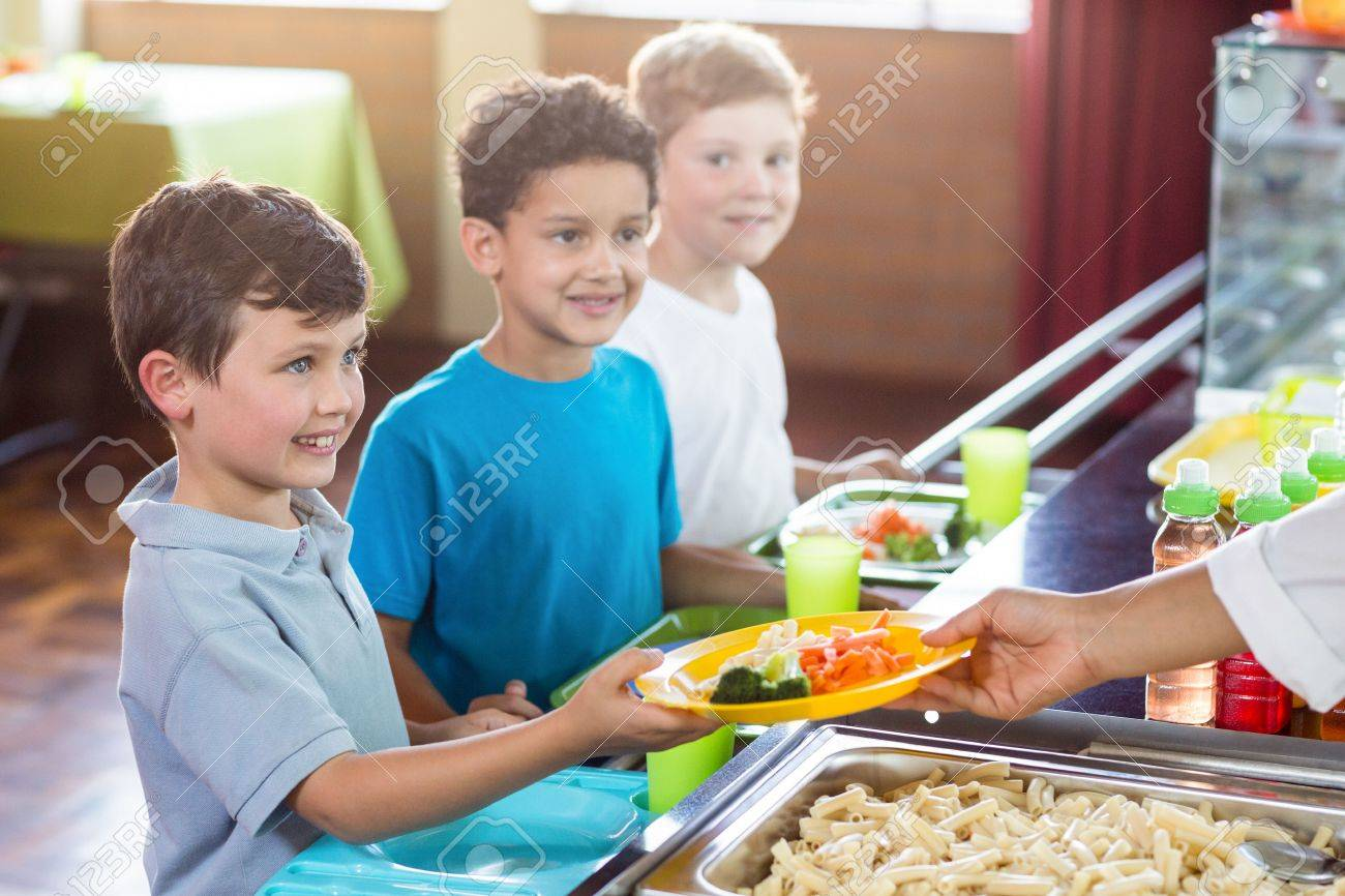 Cropped image of woman serving food to smiling schoolchildren in canteen Banque d'images - 59497971