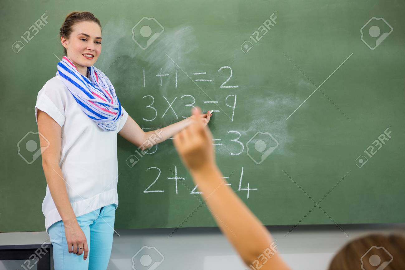 teacher teaching mathematics on chalkboard in classroom stock photo