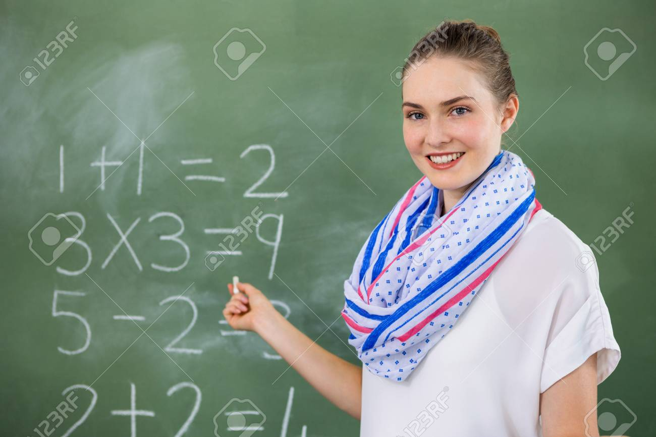portrait of teacher teaching mathematics on chalkboard in classroom