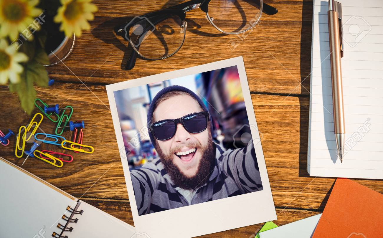 Happy Hipster Against Wooden Fence Against High Angle View Of Office  Supplies On Table Stock Photo
