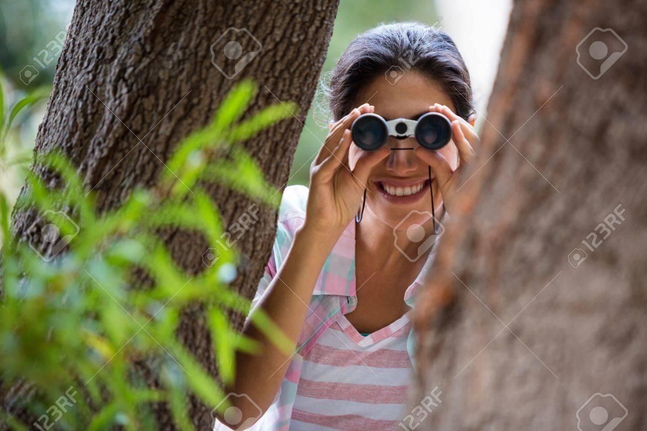 Weiblicher wanderer der durch ferngläser im wald schaut