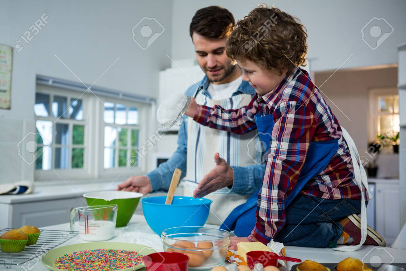 Father Teaching His Son How To Make Cupcake In The Kitchen Stock ...