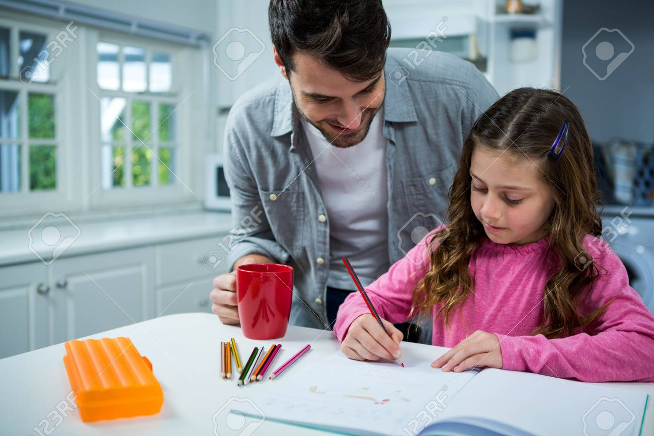 Father Helping Girl With Homework At Home In The Kitchen Stock Photo ...