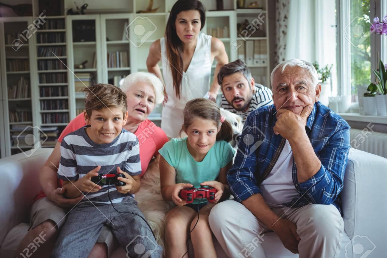 Familia Viendo A Los Ninos Jugar Videojuegos En El Hogar Fotos