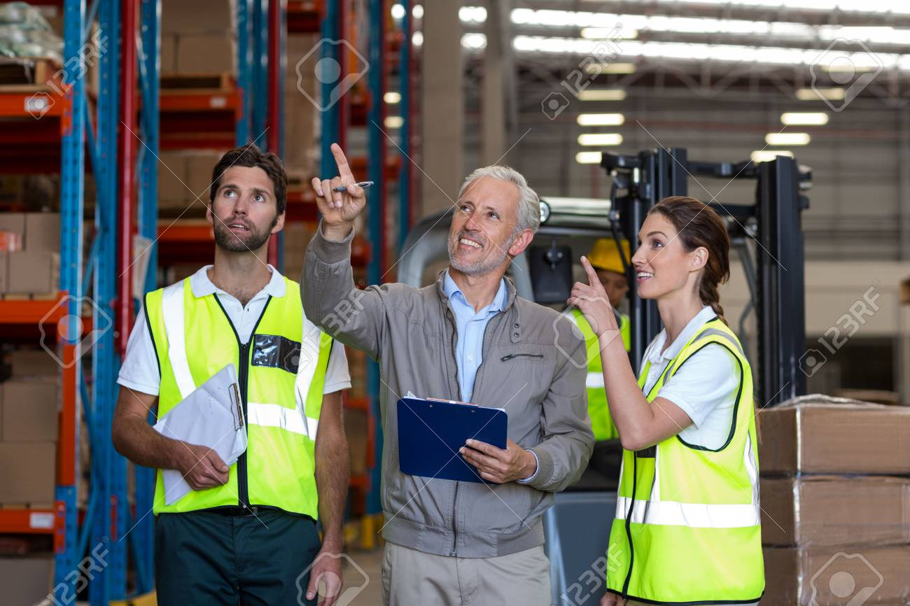 Warehouse manager and workers discussing with clipboard in warehouse - 64495644