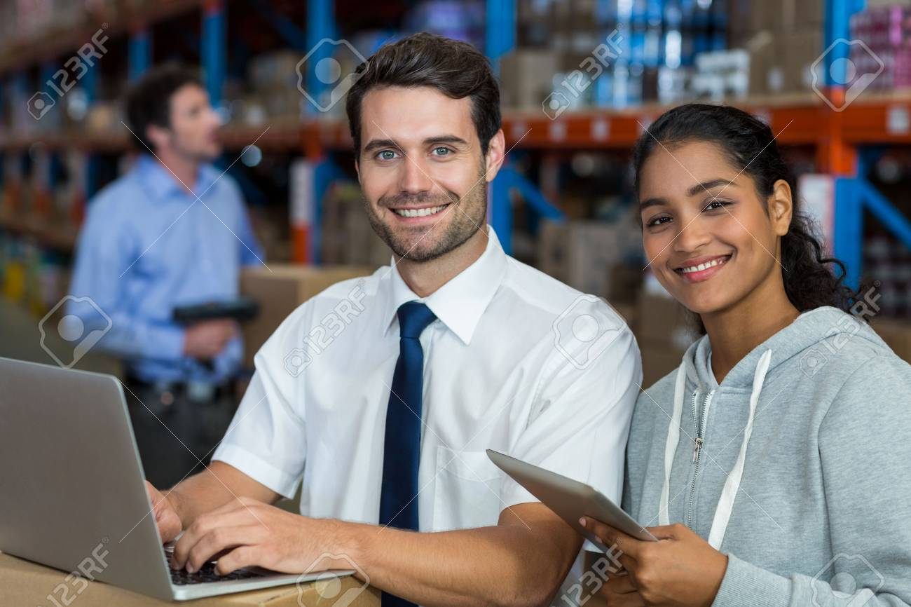 Warehouse worker working laptop and digital tablet in warehouse - 64750428