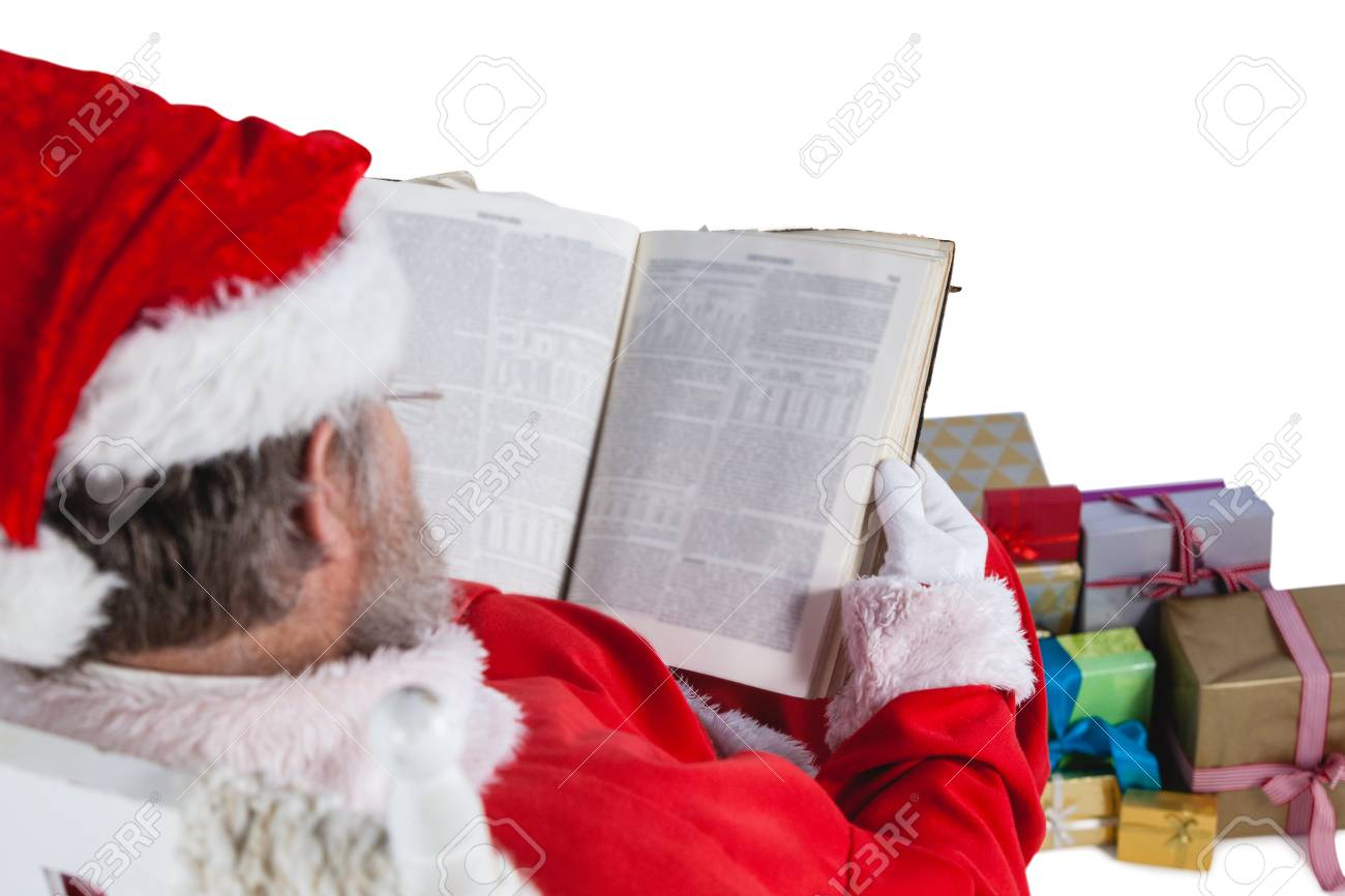 Santa Claus Reading Bible With Christmas Present Beside Him Against ...