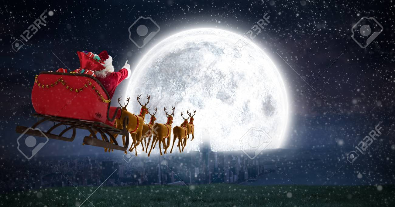 Santa Claus riding on sleigh with gift box against bright moon over city - 65428846