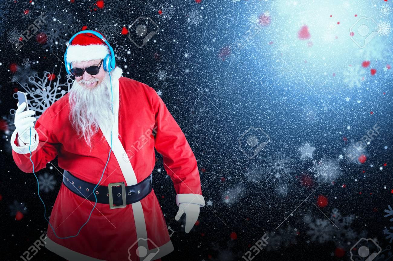 Santa Claus écoutant De La Musique Sur Les Téléphones Mobiles Contre