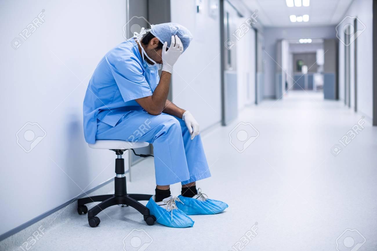 Sad surgeon sitting on a chair in hospital corridor - 66771938
