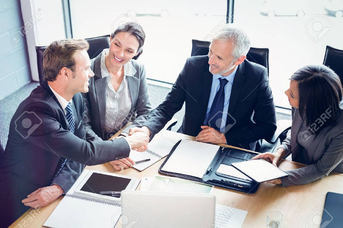 High angle view of businessmen shaking hands in conference room at office - 67356133